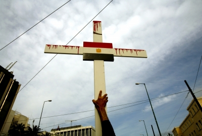 """A Coptic Christian holds up a cross in Cairo, Egypt (Courtesy Reuters)"""